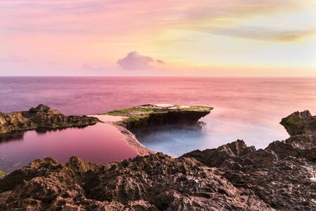 Photo pour Devil's Tear at sunset, island of Nusa Lembongan, Bali, Indonesia. Rocky shore in foreground. Tidepool and ocean pink from setting sun's reflection. Pink and yellow sky beyond. - image libre de droit