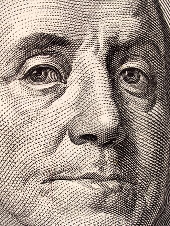 Stock macro photo of a United States one hundred dollar bill, featuring Benjamin Franklin and Independence Hall.