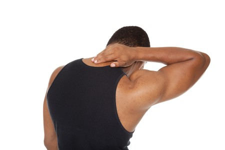Isolated studio shot of a muscular man in a fitness outfit experiencing neck pain.