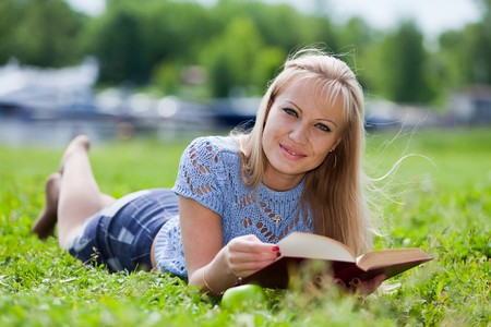 The beautiful young woman  lies on a grass in park with the book and an apple.