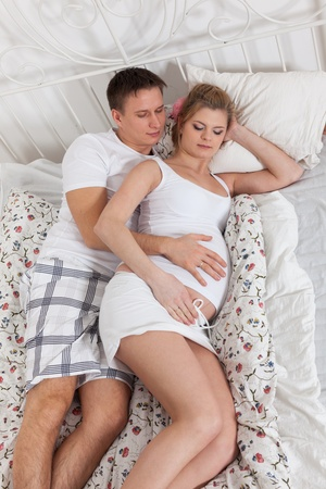 Happy pregnant family  lies on the house bed.