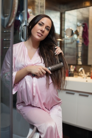 Young pregnant woman brushes long hair in a bathroom.