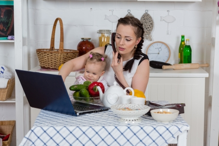 Photo for Young mother  with   little child sit at the dining table in the home kitchen. - Royalty Free Image