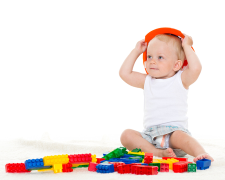 Photo pour Sweet small baby with helmet and toy  building bricks  on a white background - image libre de droit