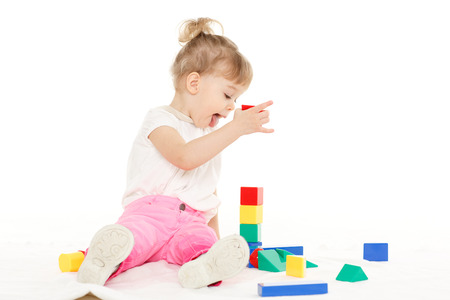Little pretty girl plays with children blocks set on a white background