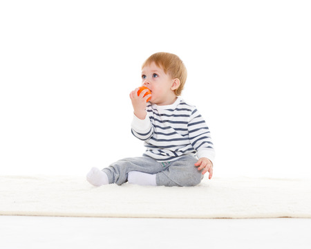 Little sweet boy plays with small orange ball on a white background.