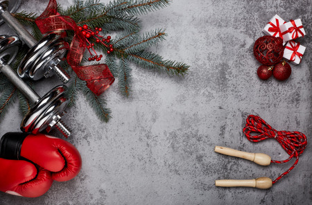 Foto de Dumbbells, boxing gloves, rope,  fir tree branches and Christmas decorations on a gray background.Top view with copy space. New Year and Christmas. Fitness, sport and healthy lifestyle concept. - Imagen libre de derechos