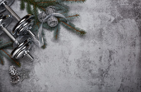 Foto de Dumbbell, fir tree branches, gifts and Christmas decorations  on a gray background. New Year and Christmas. Fitness. Healthy lifestyle. - Imagen libre de derechos