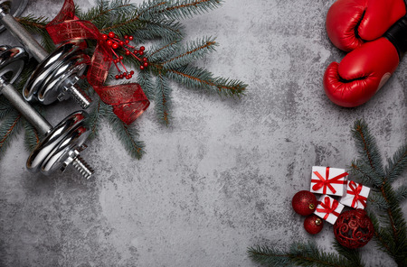 Foto de Dumbbells, boxing gloves,  fir tree branches and Christmas decorations on a gray background.Top view with copy space. New Year and Christmas. Fitness, sport and healthy lifestyle concept. - Imagen libre de derechos