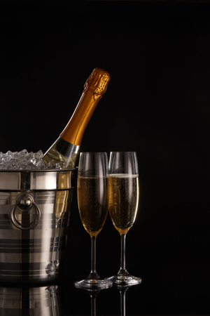 Foto de Still life with cooled champagne bottle standing in a bucket with ice and two full champagne flutes on a black background with reflection - Imagen libre de derechos