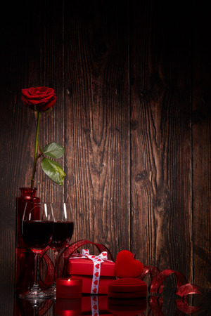 Foto de Still life with rose, red heart, gift box and two glasses with wine on a wooden background. Valentine's Day card with copy space. Design element for romantic greeting card, wedding invitation, - Imagen libre de derechos