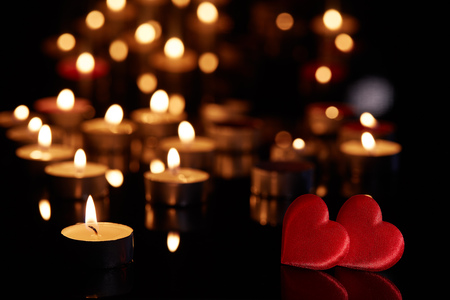 Foto de Two decorative hearts  and burning candles on a black background with reflection. Valentine's Day card. Design element for romantic greeting card, wedding invitation, - Imagen libre de derechos