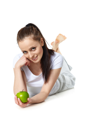 Young beautiful woman with an apple on a white background. Concept of healthy food.
