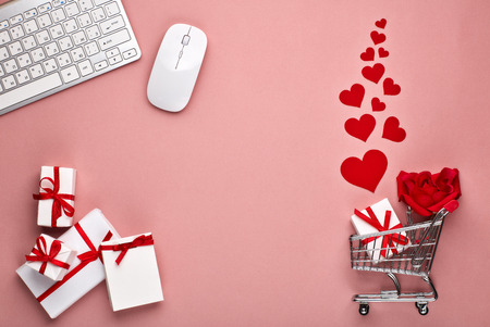 Photo for Shopping trolley, Computer keyboard and mouse, gift boxes, flower and decorative red hearts on pink background with copy space. Concept of internet shopping. Valentine's day, Mother's day, wedding - Royalty Free Image