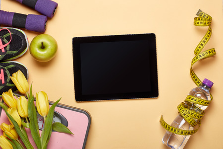 Photo for Female fitness still life. Sport accessories, computer tablet, scales, flower on yellow background. Planning of diet and trainings. Top view with copy space. Healthy lifestyle concept. Slimming Mockup - Royalty Free Image