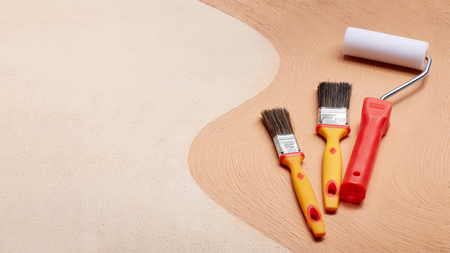 Photo pour Yellow paint brushes and red roller lying on textural double background consisting of two beige shades. Top view with copy space, Concept of construction or design office - image libre de droit