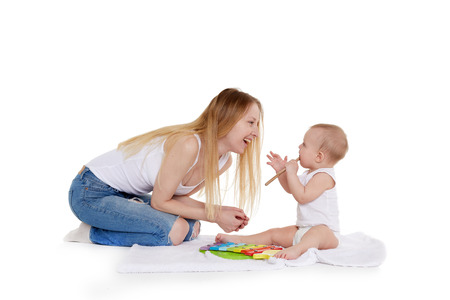 Photo pour Young woman and her daughter are playing with  developing music toy on a white background. Happy family. Eight months - image libre de droit