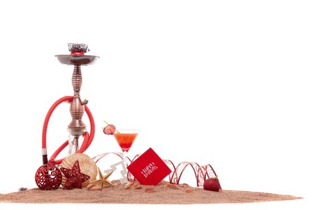 Photo for Festive beach still life: glass with cocktail, hookah (shisha), seashells, sand and christmas ornaments on white background. New Year and Christmas. Winter  vacation  in warm countries, beach holiday - Royalty Free Image