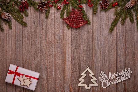 Foto de Wooden vintage background with fir tree branches, gift box and Christmas ornaments. Top view with copy space. New Year and Christmas,  For greeting card or advertising - Imagen libre de derechos