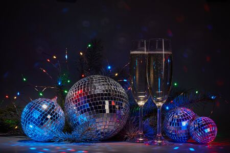 Photo pour Champagne flutes, mirror balls (disco ball), fir branch,  on dark background with colorful LED lights garland. New Year and Christmas. Weekend or holiday party. - image libre de droit