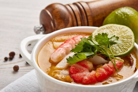 Photo pour Delicious  fish cream soup with shrimps in white bowl served with spices and lime on light wooden background. Healthy food. Seafood menu - image libre de droit