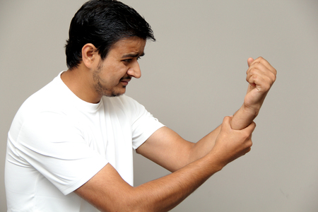 joint pain, pain in arm, expressions of young amazed man isolated on gray background