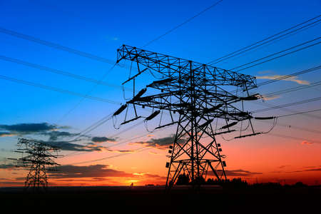 Photo for High voltage towers, silhouetted in the setting sun - Royalty Free Image