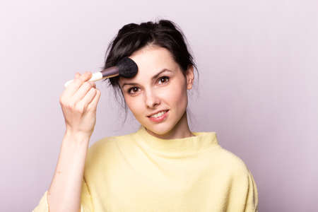 Photo for attractive woman in a yellow sweater does makeup with a brush - Royalty Free Image