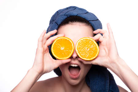 Photo for funny woman after shower in a towel on her head holds an orange, skin care, vitamins, fruits - Royalty Free Image