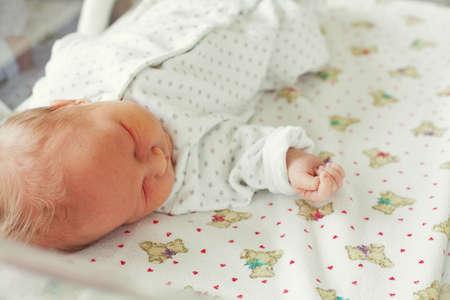newborn baby sleeping in hospital basinet