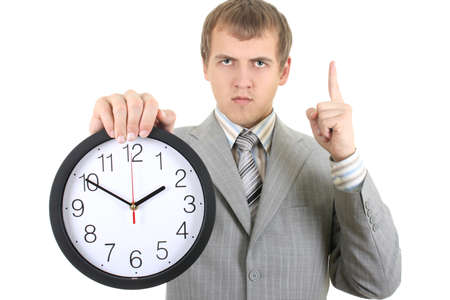 young serious businessman holding a clock over white