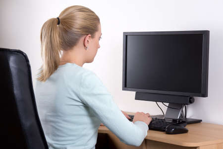 back view of young woman with personal computer in office