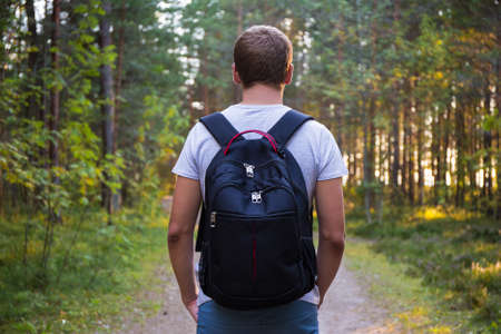 rear view of man with backpack hiking in forest