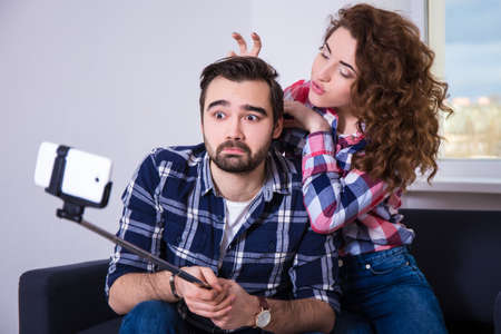 happy funny couple taking photo with cell phone on selfie stick st home