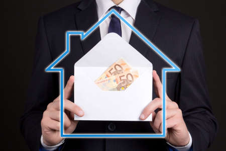 real estate and mortgage concept - close up of envelope with money in business man hands