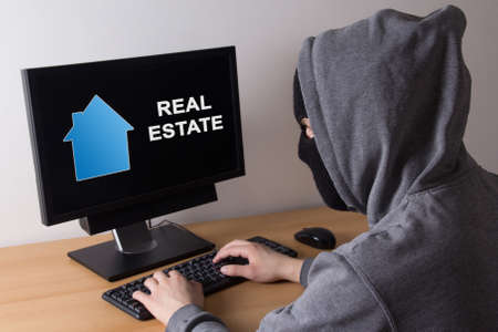 Photo pour criminal and burglary concept - thief in mask searching info about real estate in internet - image libre de droit