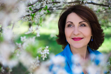 Photo pour close up portrait of happy middle aged woman in blooming summer garden - image libre de droit