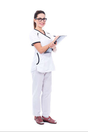 full length portrait of young beautiful woman doctor writing something on clipboard isolated on white background