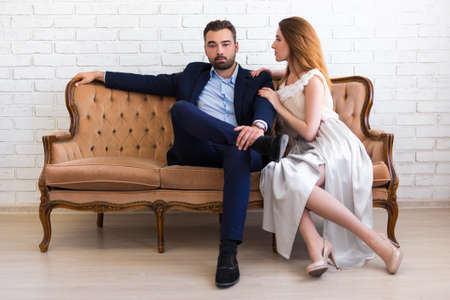 Photo pour richness and success concept - handsome bearded man in business suit sitting on vintage sofa with beautiful girl - image libre de droit