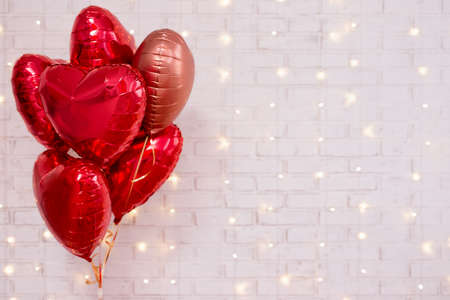 Photo pour Valentine's day background - group of red heart shaped balloons over white wall with shiny lights - image libre de droit