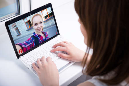 Photo pour girl chatting with friend over a video call at home - image libre de droit