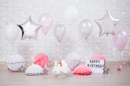 Foto de first birthday background - cake, helium balloons and lightbox with happy birthday text - Imagen libre de derechos