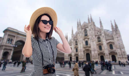 Photo pour portrait of young beautiful woman tourist in straw hat with camera over Duomo cathedral in Milan, Italy - image libre de droit