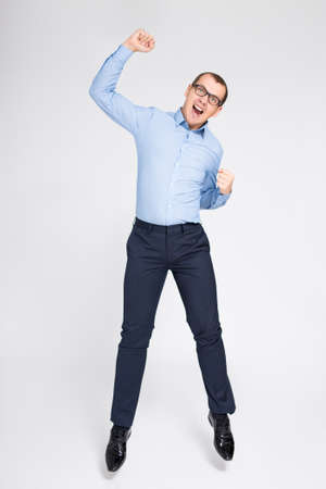 Foto de success concept - cheerful young handsome businessman celebrating something and jumping over gray background - Imagen libre de derechos