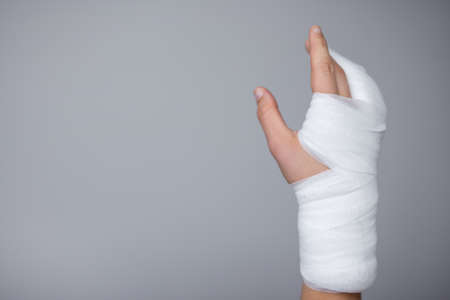 injury and first aid concept - male hand wrapped in bandage and gypsum over gray background with copy space