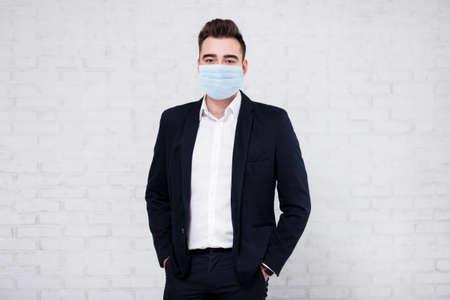 Photo pour coronavirus, pandemic, quarantine, health care and office work concept - portrait of handsome businessman and copy space over white brick wall background - image libre de droit