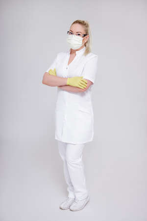 health care, medicine, cosmetology and corona virus pandemic concept - full length portrait of doctor, nurse or cosmetologist in white uniform posing over gray background