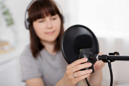 Photo for content making, podcast and blogging concept - woman preparing microphone for audio podcast recording in home office - Royalty Free Image