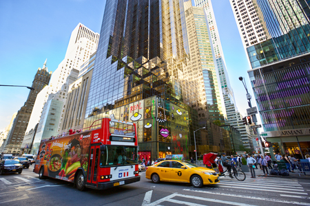 New York, New York, USA - September 16, 2016: Busy traffic on Fifth Avenue with cars, taxi cab, touristic bus end pedestrians in Midtown Manhattan
