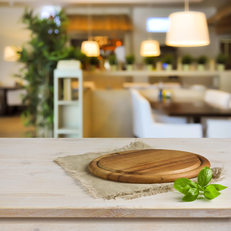 Photo pour Cutting board on table over blurred restaurant interior background - image libre de droit